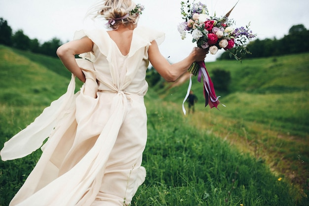 Woman running with the wedding dress and a bouquet Premium Photo