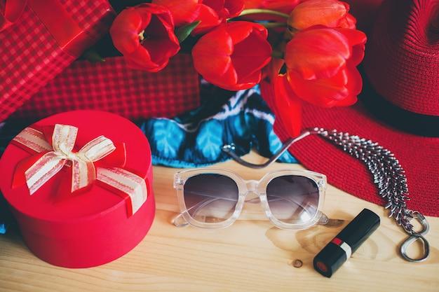 Женские аксессуары и красные тюльпаны на столе Бесплатные Фотографии