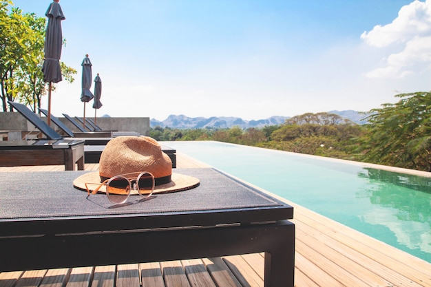 Woman's accessories for summer on chaise lounge poolside on the roof top hotel. Premium Photo
