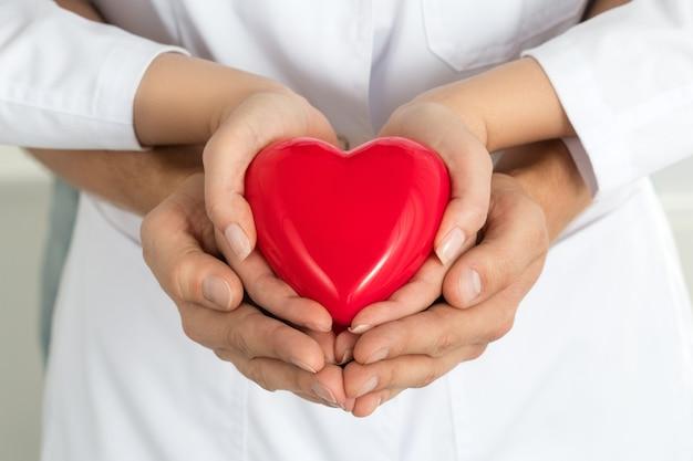 女と男の手が赤いハートを一緒に保持しています。愛、援助、ヘルスケアのコンセプト Premium写真