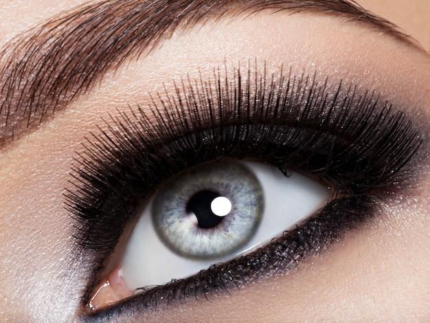 Woman's eye with black eye makeup. macro style image. long eyelashes Free Photo