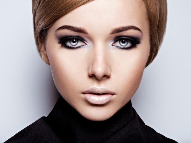 Volto di donna con trucco moda nero dell'occhio e lunghe ciglia nere. Foto Gratuite