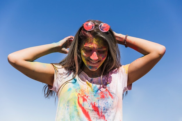 Woman's face with holi colors standing against blue sky Free Photo