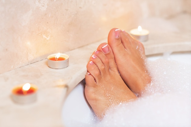 Woman's feet in bath foam . relaxation in hotel or spa. Premium Photo
