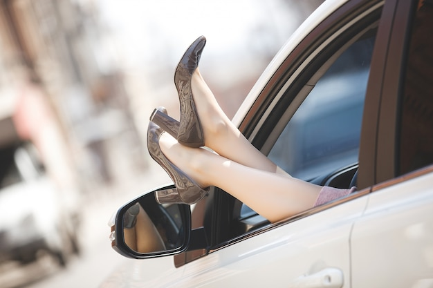 Woman`s feet in the car. unrecognizable woman in the automobile. lady`s shoes out of the car`s window. female legs. Premium Photo
