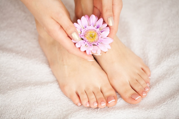 Woman's french pedicure. close up woman hands touching long legs, soft skin. hair removal Premium Photo
