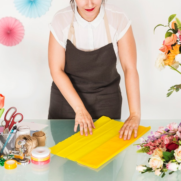 Woman's hand arranging yellow cloth for making flower bouquet on desk Free Photo