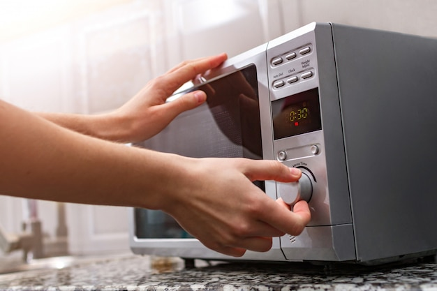 Woman's hand closing the door of the microwave oven and sets the time for heating food Premium Photo