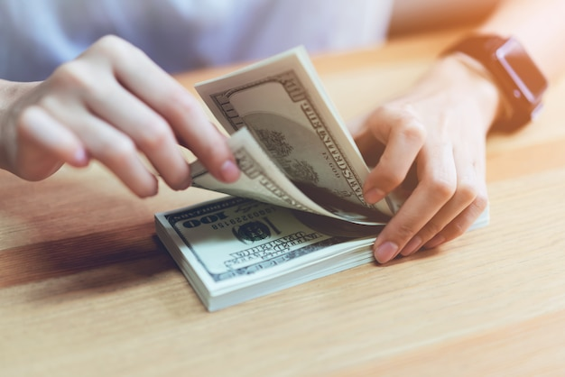 Woman's hand counting money 100 dollars. the concept of spending by cash. Premium Photo