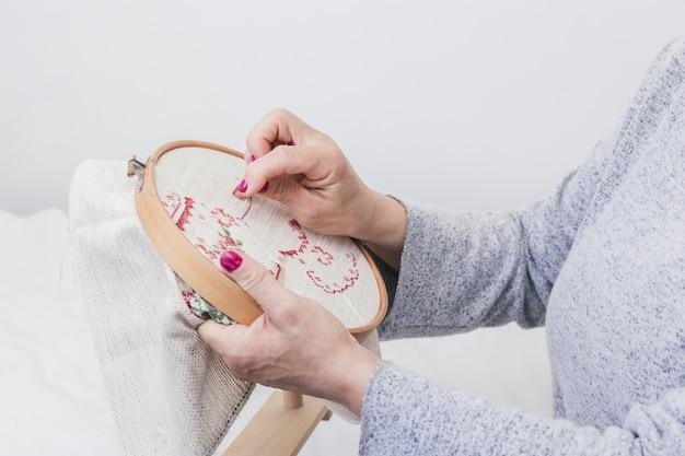 Modello di cucitura a croce a mano della donna su un cerchio su sfondo bianco Foto Gratuite