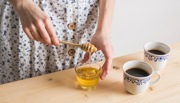 Woman's hand dripping the honey in glass with cup of tea cups on wooden desk Free Photo