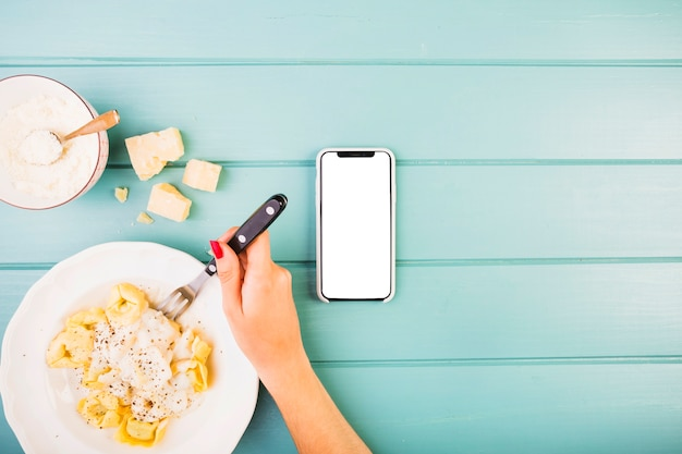 Woman's hand eating pasta with smartphone on desk Free Photo