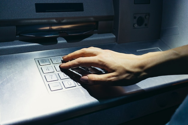 Woman's hand enters the secret code at the atm on the street at night Premium Photo