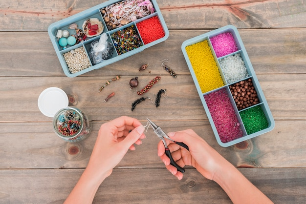 Woman's hand fixing the hook on beads with plier on wooden desk Free Photo