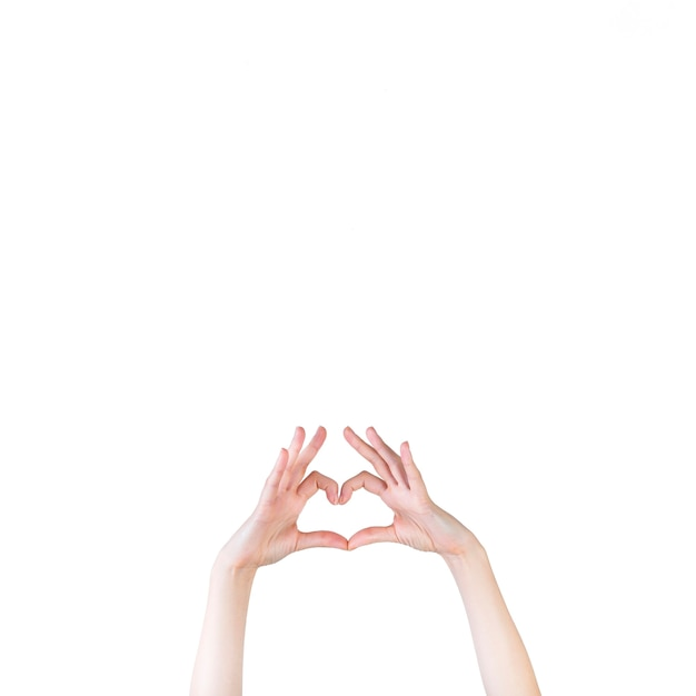 Woman's hand forming heart shape over white background Free Photo