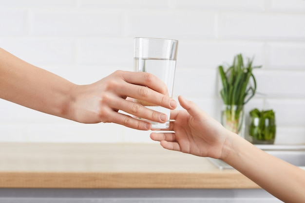 Woman's hand gives a glass of purified water to her child. concept purification of water Premium Photo