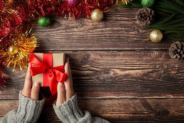 Женская рука держит подарочную коробку с красной лентой на деревянном полу Бесплатные Фотографии