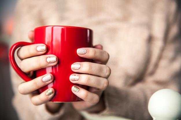 コーヒーの赤いカップを持っている女性の手。美しい冬のマニキュア付き。 Premium写真