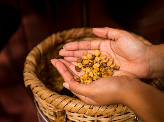 Woman's hand holding coffee beans over wicker basket Free Photo