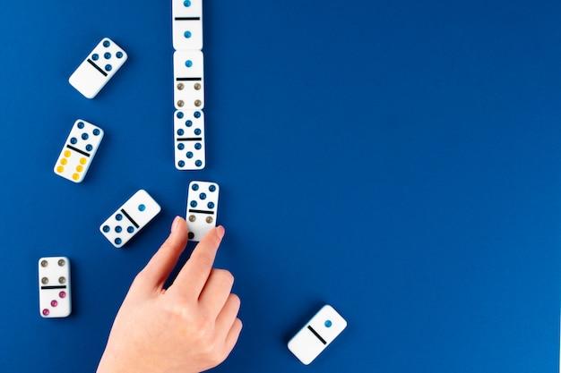 Woman's hand holding domino piece Premium Photo