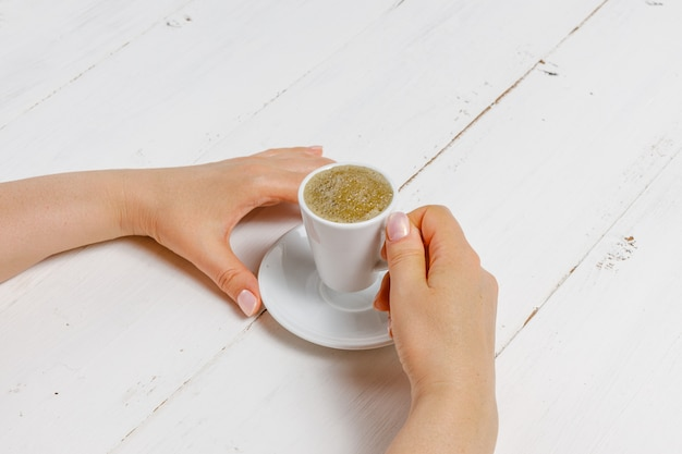 A woman's hand holding an espresso cup Premium Photo