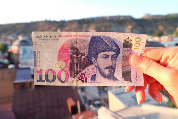Woman's hand holding georgian 100 lari banknote with blurry tbilisi aerial view in background Premium Photo