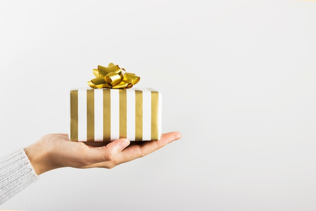 Woman's hand holding a gift in white and gold paper on gray, copy space Premium Photo
