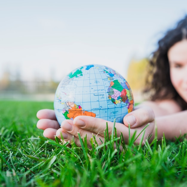 Woman's hand holding globe over green grass Free Photo
