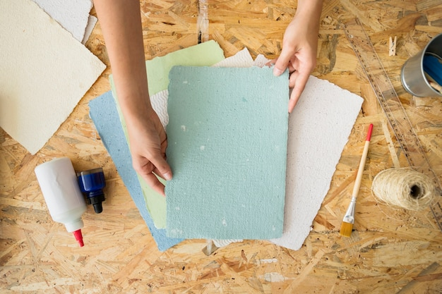 Woman's hand holding handmade paper over wooden desk Free Photo