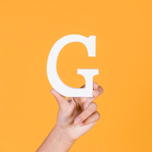 Woman's hand holding the white capital letter g Free Photo