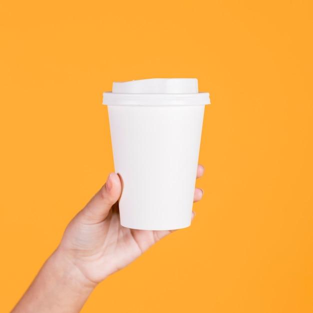 Женская рука держит белый одноразовый стакан на желтом фоне Premium Фотографии
