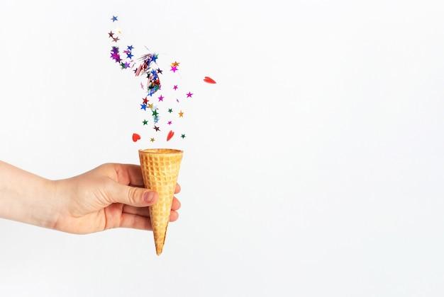 Женская рука держит вафельный рожок и падающее конфетти на белом фоне Premium Фотографии