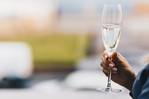 Woman`s hand holds glass of white wine, celebrates something together with friends, blurred background Premium Photo