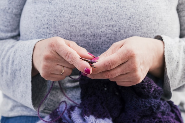 Woman's hand knitting the wool scarf with knitted needles Free Photo
