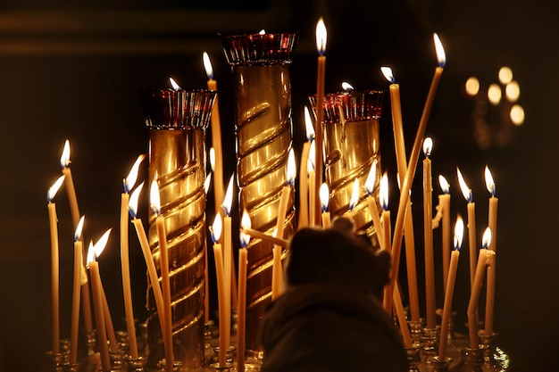 Woman's hand lights a candle in the dark church Premium Photo