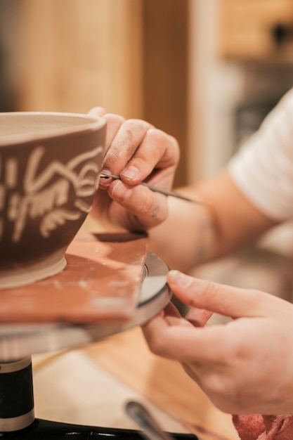 Woman's hand making design on painted bowl Free Photo
