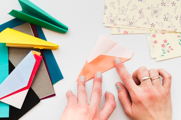 Woman's hand making paper airplane on white backdrop Free Photo