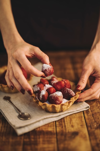 Woman's hand making strawberries tart on wooden table Free Photo