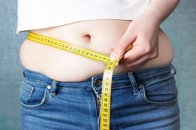 Woman's hand measure her stomach with a tape measures Premium Photo