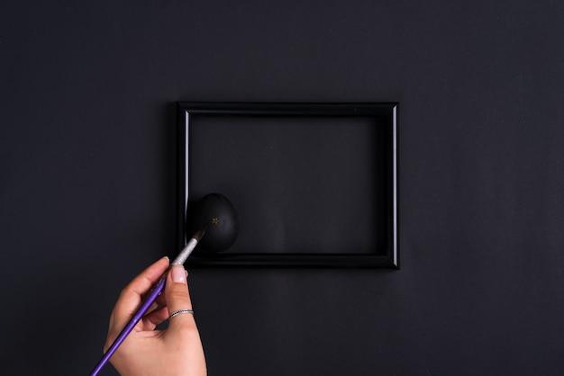 女性の手は、同じ色のフォトフレームと背景に黒い色で絵筆でイースターエッグをペイントします。 Premium写真