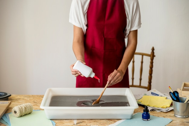 Woman's hand pouring glue in paper pulp on wooden desk Free Photo