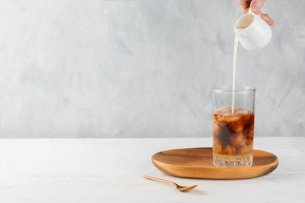 Рука женщины лить овсяное молоко в холодный кофе со льдом в стакане на деревянный поднос, селективный фокус, copyspace Premium Фотографии