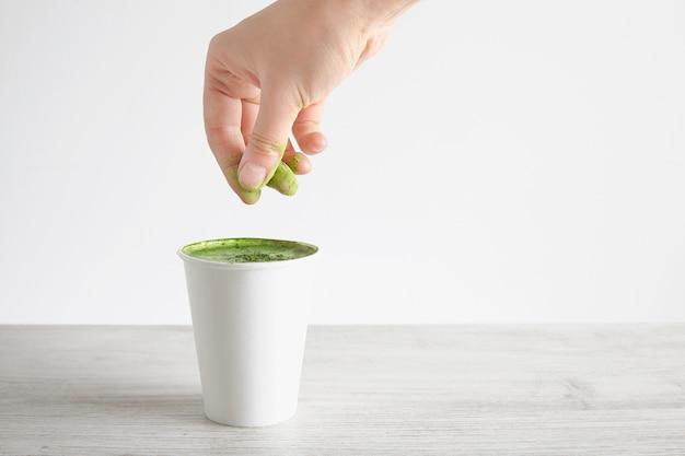 女性の手は、木製のテーブル、白い背景で隔離の持ち帰り用の紙ガラスの上の抹茶ラテに緑の有機プレミアム抹茶パウダーを注ぐ 無料写真