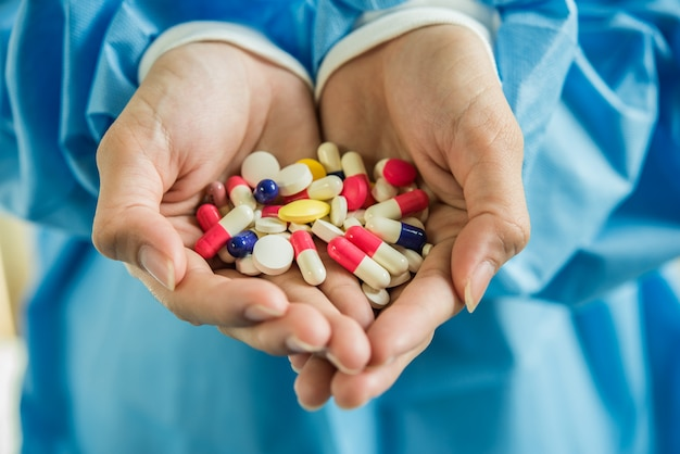 Woman's hand pours the medicine pills out of the bottle Free Photo