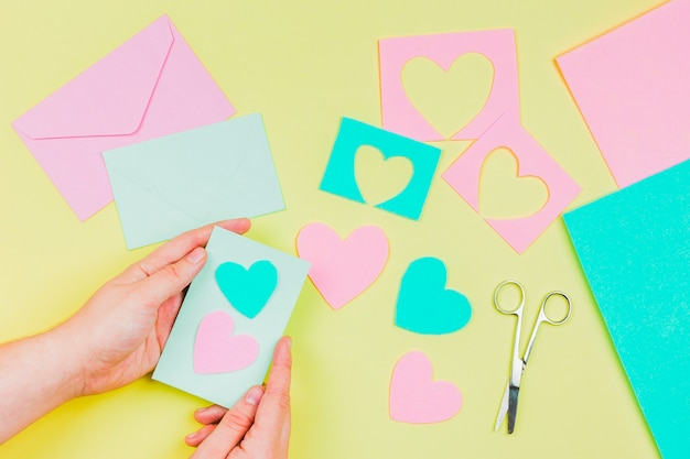Woman's hand preparing heart shape greeting card on yellow background Free Photo