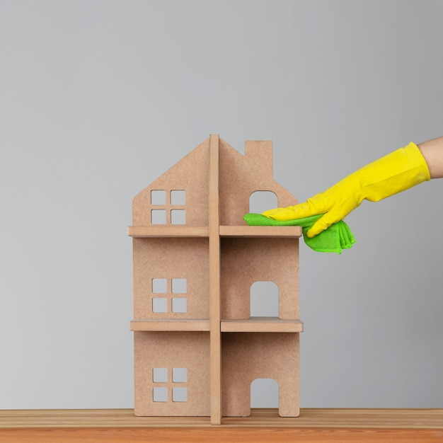 A woman's hand in a rubber glove washes the symbolic house with a green cloth. the concept of spring cleaning and cleanliness. Premium Photo