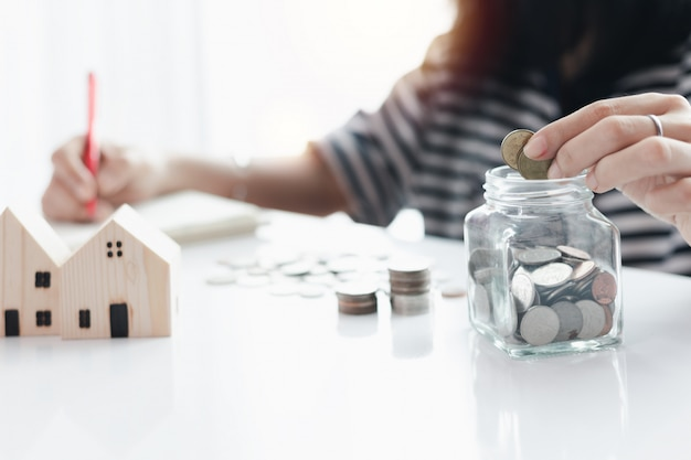 Woman's hand saving a coin into the glass jar for planning, housing and property financial concept Premium Photo