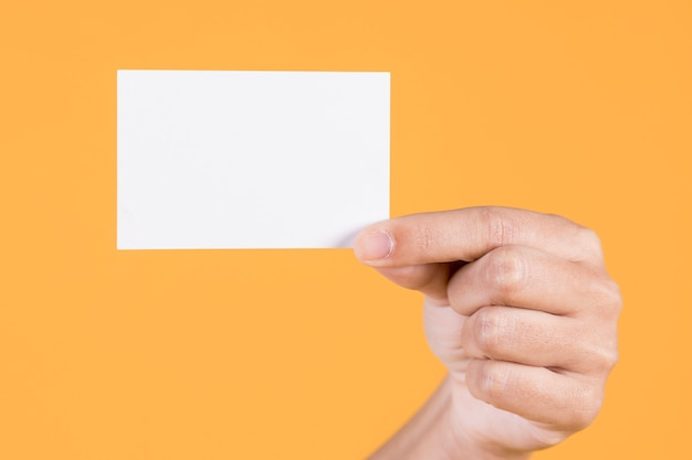 Woman's hand showing blank white visiting card against yellow background Free Photo