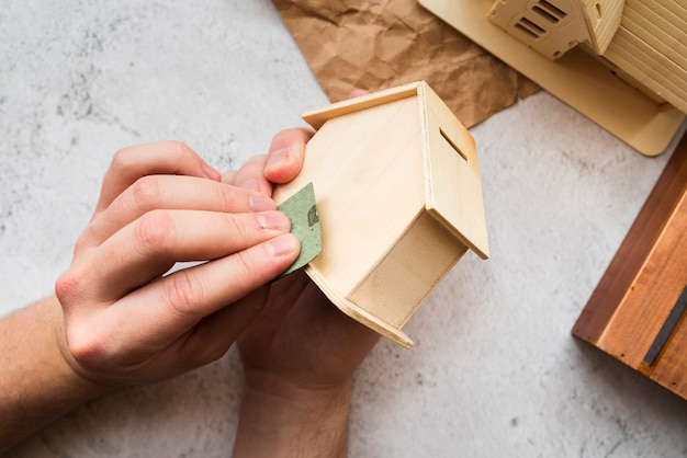 Woman's hand smoothing the wooden piggybank house Free Photo