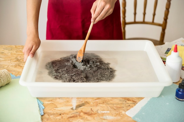 Woman's hand stirring paper pulp in water Free Photo